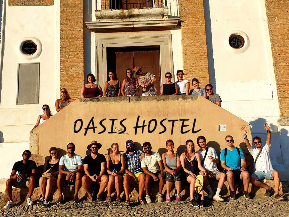 Una foto di un gruppo di persone felici di fronte all'ostello Oasis