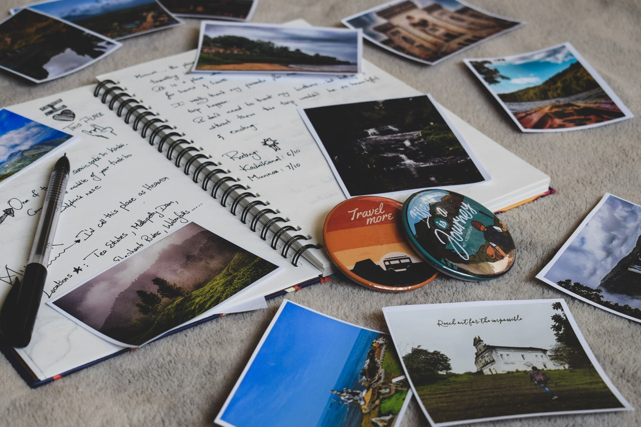 An open travel journal with photos and badges scattered around it ready to be inserted.