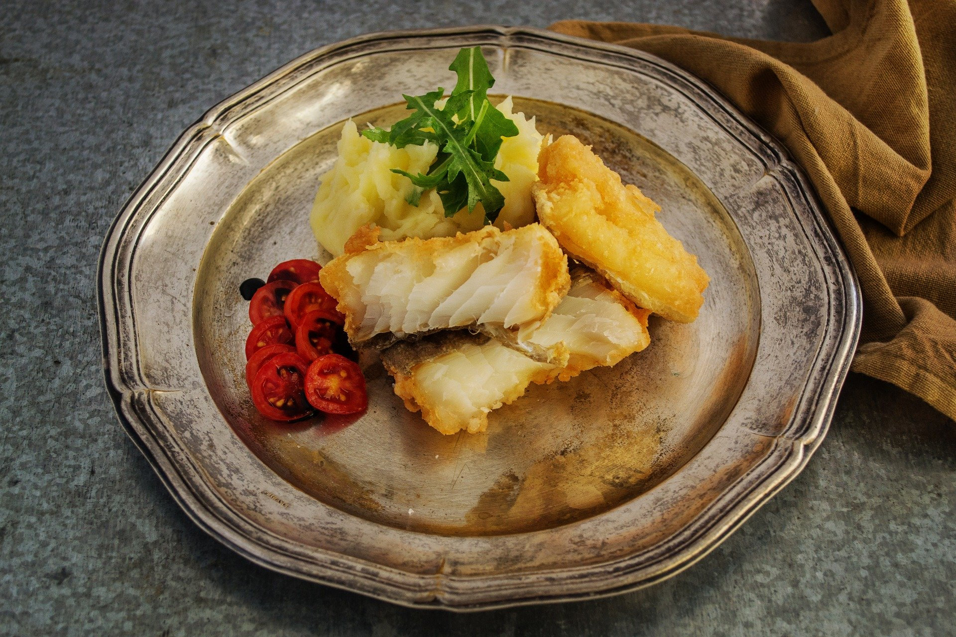 A closeup on a plate with codfish, potatoes and cherry tomatoes