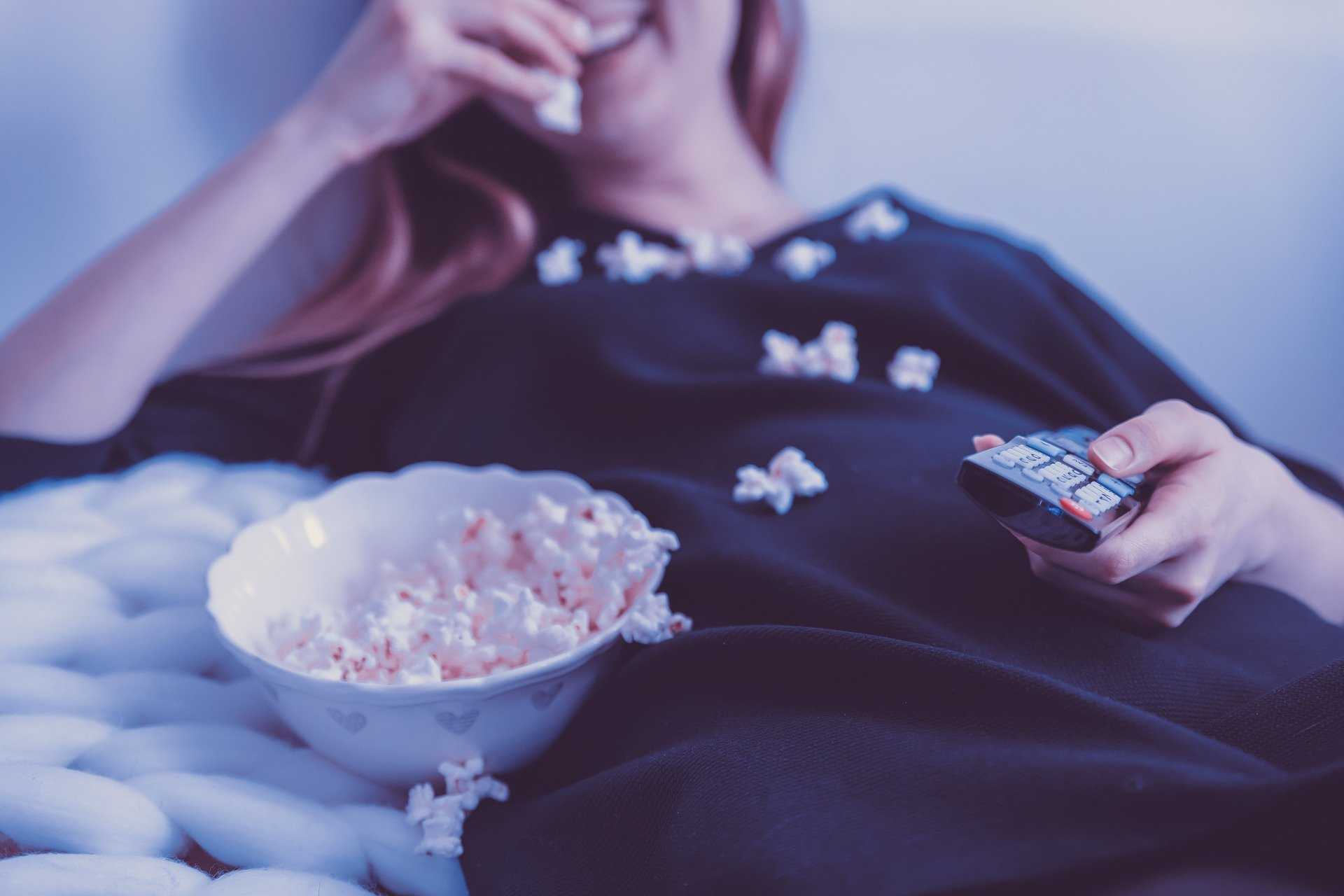 A close up of a young lady sat back eating popcorn as she changes the tv channel with the remote control.