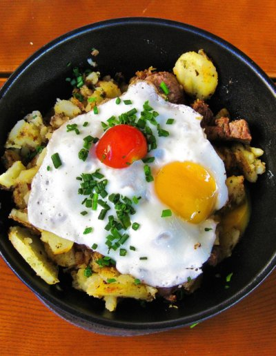 Huevos Rotos cooked in a frying pan on top of a table