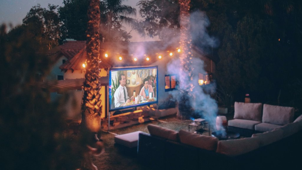 A night time image of a small cinema setup in a backyard with furniture set out, fairy light hung and trees surrounding