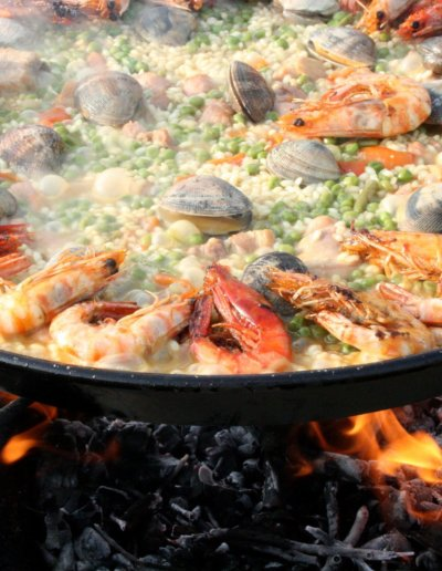 A Paella being prepared in a big frying pan on a barbecue grill