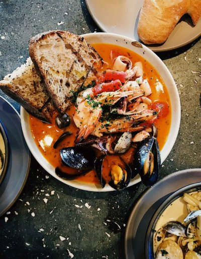 A hot spanish dish with bread and seafood