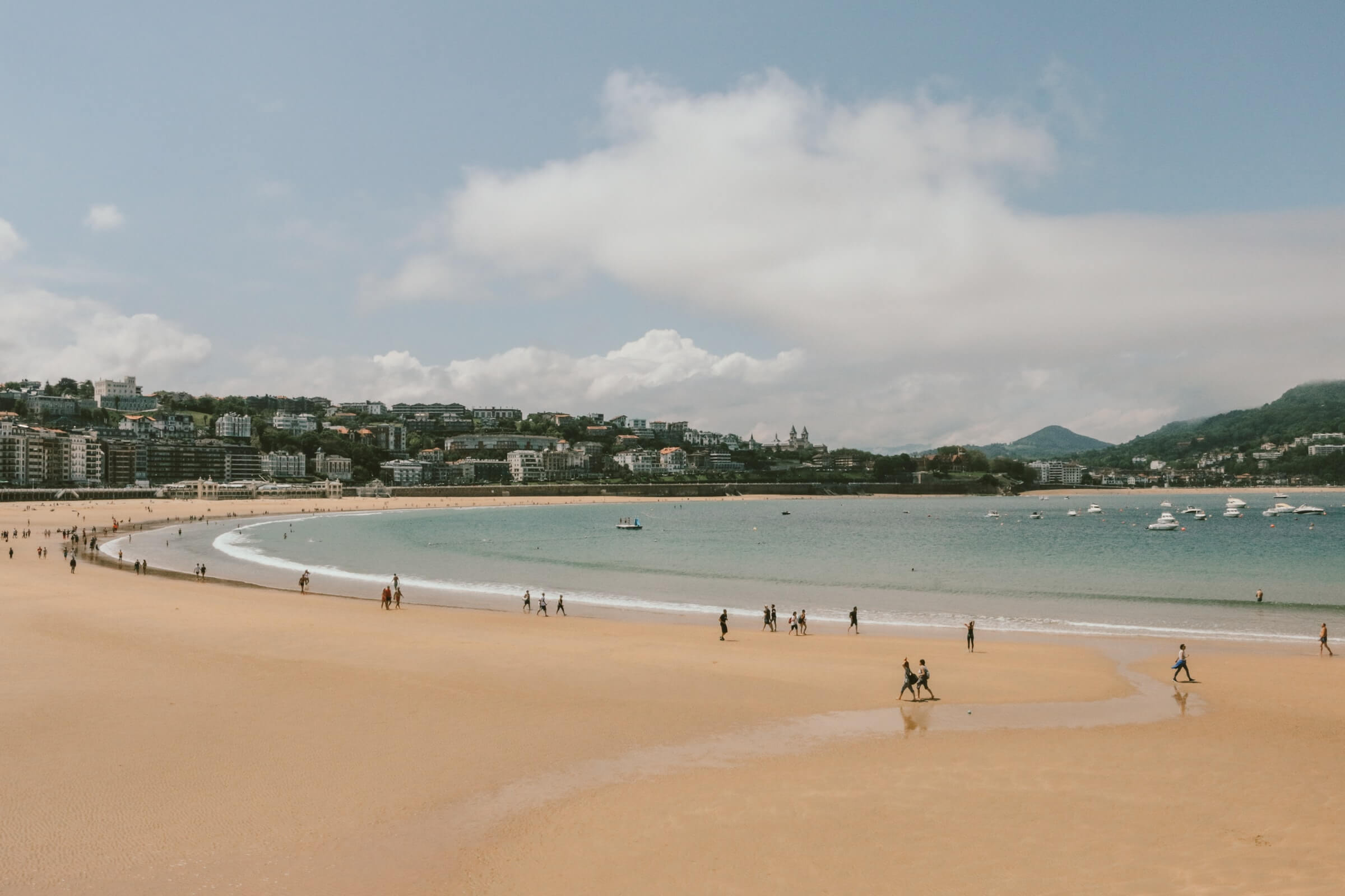A wide view of a beach in Spain with a few people on the sand