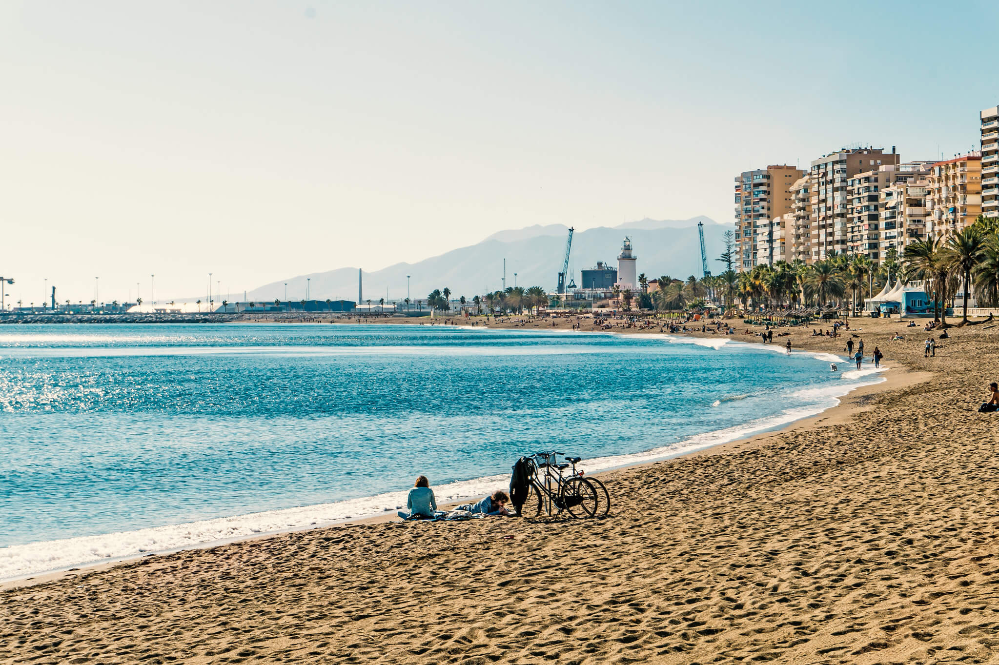 La Malagueta Beach, in Malaga, Spain, a couple chilling at the sand