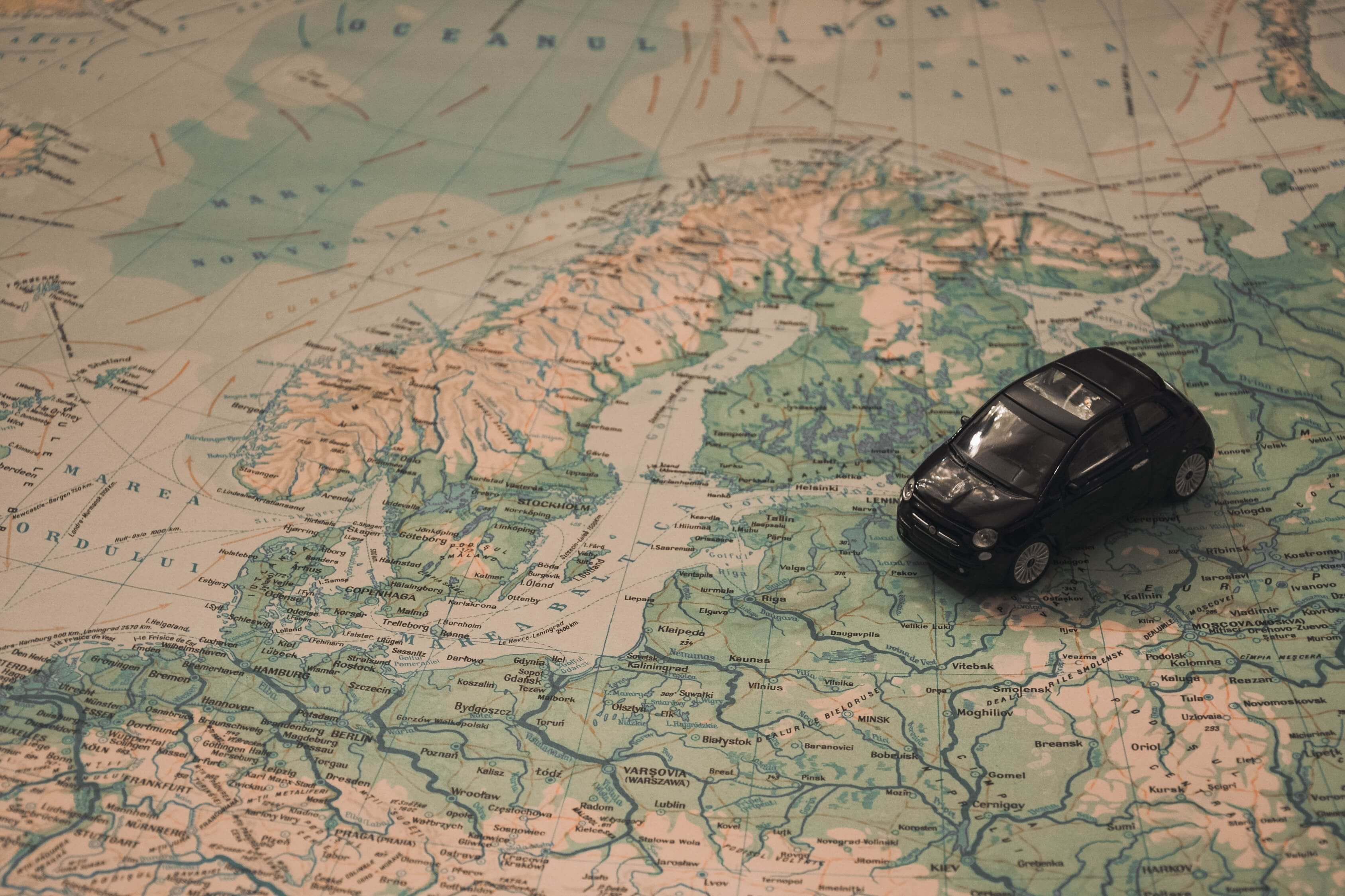 A plastic toy car on top of a map