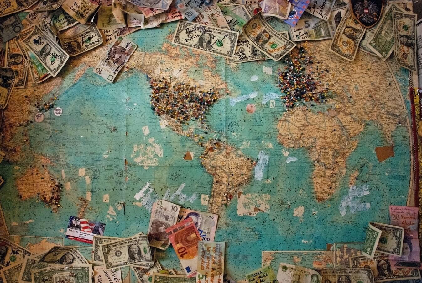 Un sacco di soldi, monete e banconote in cima a una mappa del mondo
