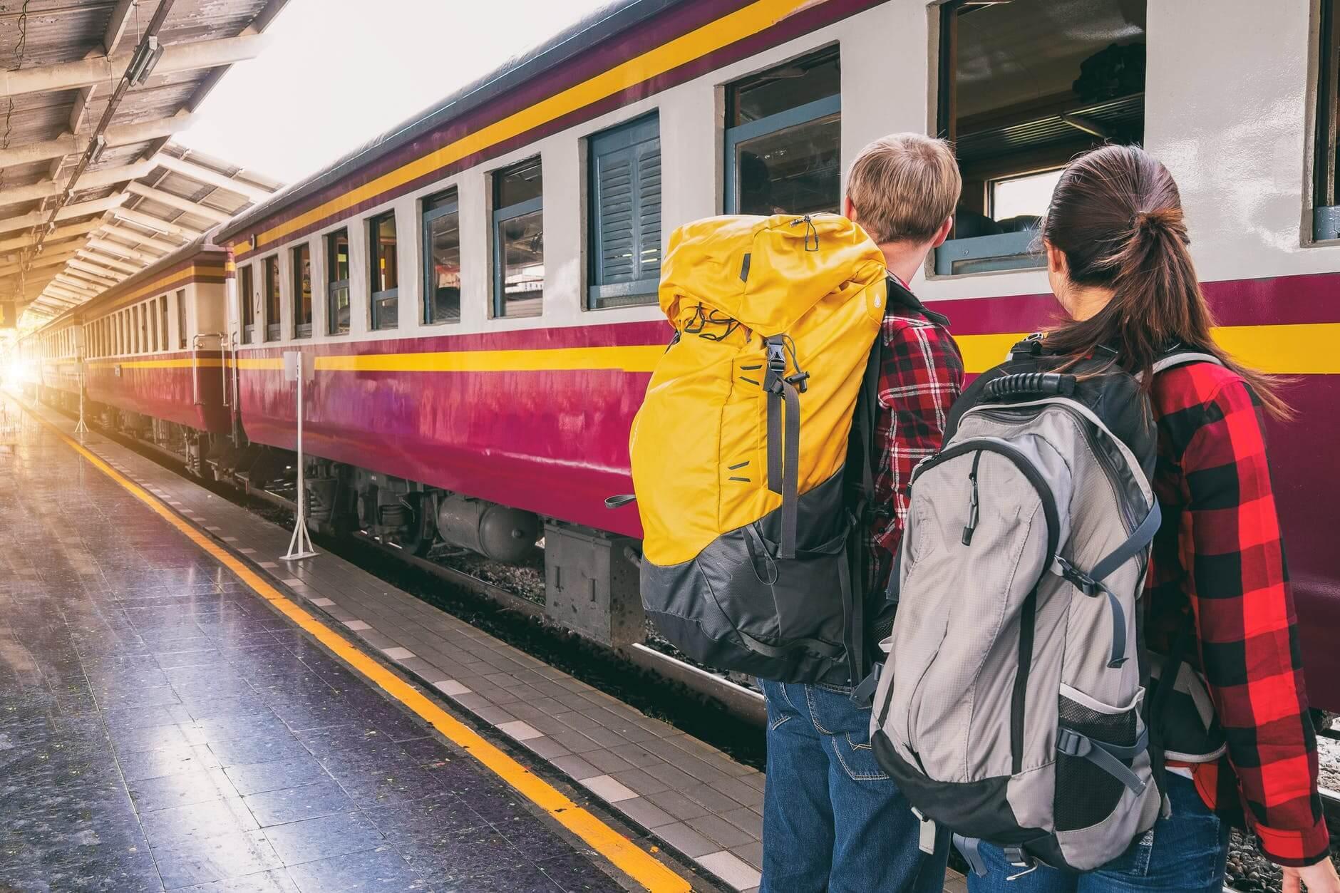 Una coppia di backpackers (uomo e donna) in attesa di prendere un treno in una stazione