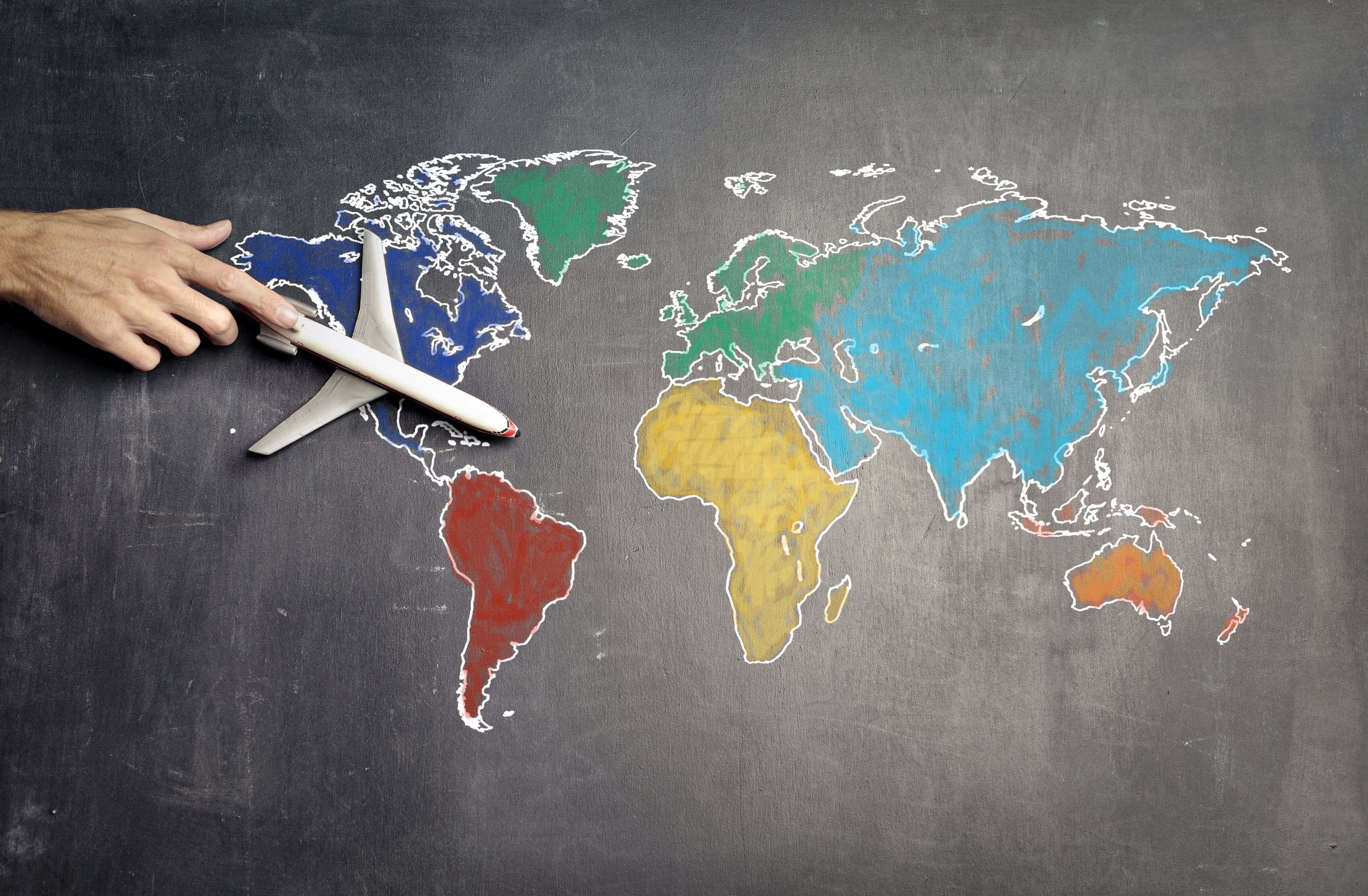 Un aereo giocattolo in cima a un disegno della mappa del mondo